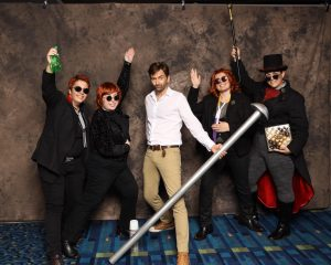 Four Crowley cosplayers pose with David Tennant, who is holding the giant pin. Costumes featured are modern era with a spray bottle, 60s with a thermos, 00s with a nonbinary pride flag scarf, and 1800s from a deleted scene with a box of chocolates.