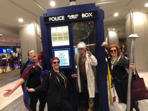 As the coming out party winds down, four cosplayers pose in front of a perfect replica of the TARDIS. From left to right, two Crowleys gesturing dramatically with their arms, an Aziraphale (standing inside the TARDIS), and another Crowley, leaning on the side and casually holding the giant pin prop