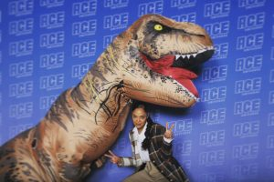 Tessa Thompson and a fan in a dinosaur costume at Ace Comic Con