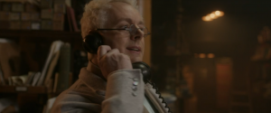 "Good Omens Deleted Scene where Aziraphale smiles kindly as he talks on the phone. He is wearing his ""nifty"" reading glasses and his gray housecoat sweater"
