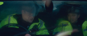 Good Omens Deleted Scene where two highway workers in yellow vests sit in the front seat of a car and frantically radio for help as fish fall from the sky and splat against their windshield