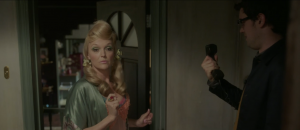 Good Omens Deleted Scene where Madame Tracy talks with Newt Pulsifer. Madame Tracy is wearing a blonde wig, heavy makeup, and sultry loungewear. Newt is wearing a brown jacket and looking intently at a telephone.