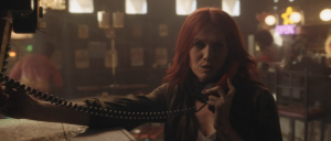 Good Omens Deleted scene with War in a seedy bar talking on a corded telephone. She looks annoyed.