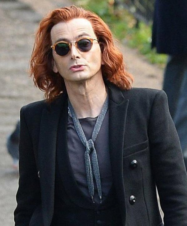Of all of Crowley's looks in Good Omens, the late aughts is one of his most non-binary eras. He wears a black blazer with thin lapels, a black feminine cut vest, a fashion scarf, women's tortoiseshell sunglasses, and his red hair is long and wavy.