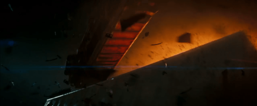A screenshot from the movie, Super 8. A train car flies through the air with an explosion and debris behind it. It's nighttime and everything is dramatically lit.