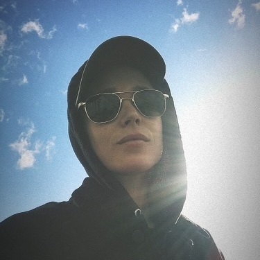 An androgynous person wears sunglasses, a baseball cap, and a hoodie with the hood up. Behind them is a blue sky with small clouds and bright sunlight