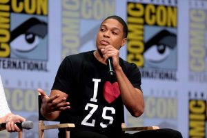 """Ray Fisher sits on stage at ComicCon, holding a microphone and wearing a shirt that reads """"I Heart ZS"""""""